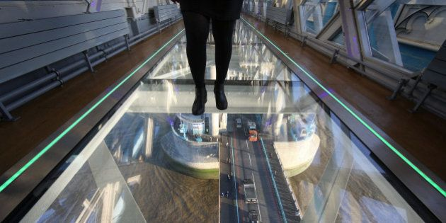 LONDON, ENGLAND - NOVEMBER 10: A visitor crosses Tower Bridge's new glass walkway on November 10, 2014...