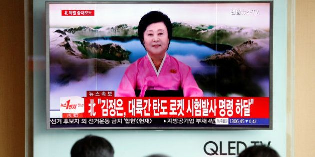 People watch a TV broadcast of a news report on North Korea's Hwasong-14 missile, a new intercontinental...