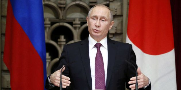 Russian President Vladimir Putin gestures as he speaks during a joint news conference with Japanese Prime...