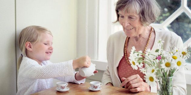 Girl pouring tea into a tea cup and her grandmother sitting beside