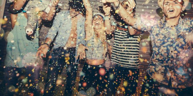 Teenagers enjoying confetti in front of roller door whilst partying in