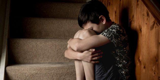 Sad, bullied or abused boy crying sitting on