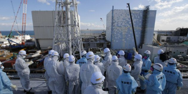 Members of the media, wearing protective suits and masks, receive briefing from Tokyo Electric Power...