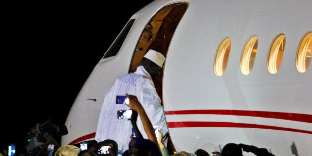 Former Gambian president Yahya Jammeh boards a private jet before departing Banjul airport, Gambia January...