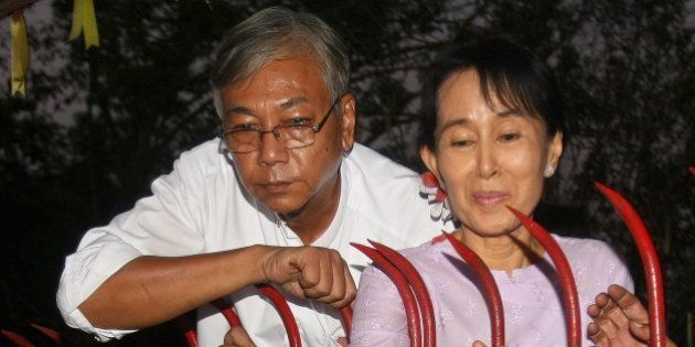 Myanmar's opposition leader Aung San Suu Kyi (R) appears with Htin Kyaw (L) a senior National League...