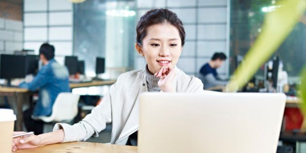 young asian business woman working in office using laptop