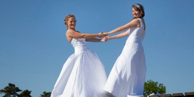 two brides on wooden bridge against blue sky background hold each