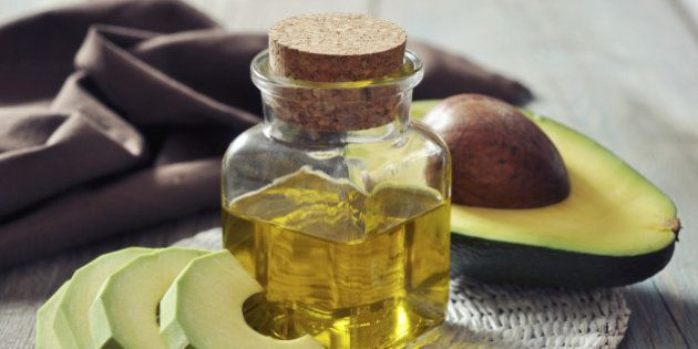 bottle of avocado essential oil with fresh avocado fruit