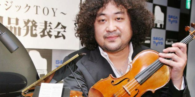 Tokyo, JAPAN: Japanese violinist Taro Hakase poses next to the world's smallest grand piano 'Grand Pianist',...