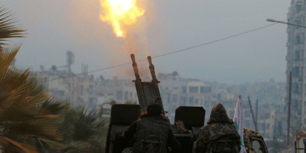 Free Syrian Army fighters fire an anti-aircraft weapon in a rebel-held area of Aleppo, Syria December...