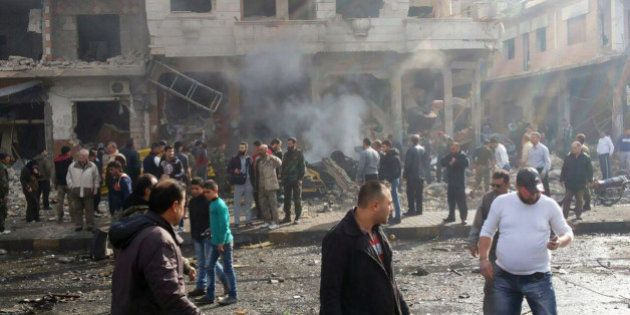In this photo released by the Syrian official news agency SANA, Syrian citizens gather at the scene where...