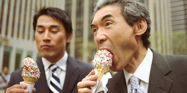 Two businessmen eating ice