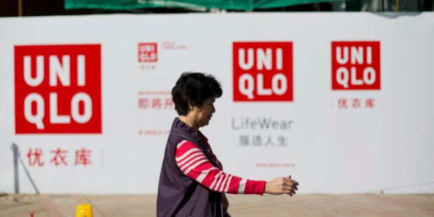A woman walks past an advertisement for Uniqlo, operated by Fast Retailing Co., at a construction site...