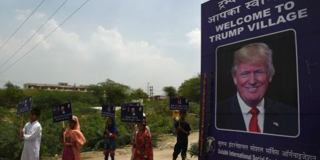 Indian children hold placards next to a billboard with the image of US President Donald Trump by the...