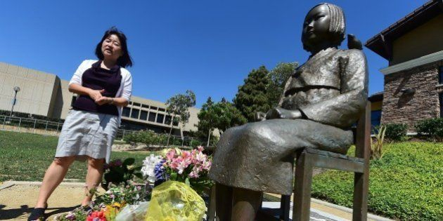 Activist Phyllis Kim of the Korean American Forum of California, stands beside the controversial Comfort...