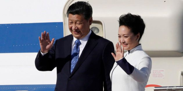 Chinese President Xi Jinping, left, and his wife Peng Liyuan wave upon arrival Tuesday, Sept. 22, 2015,...