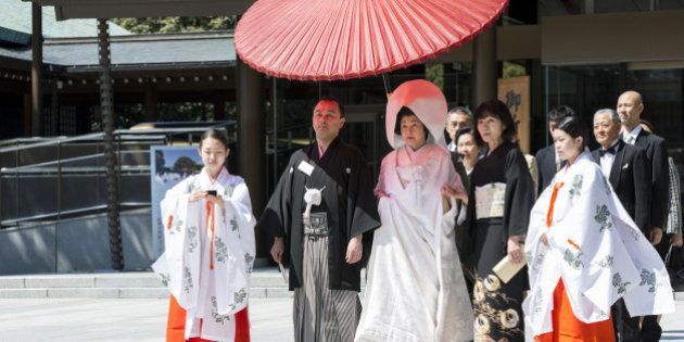 Japanese bride and groom with family and shrine maidens (Miko) at Shinto wedding ceremony, Meiji Jingu...