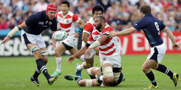 Japan's captain Michael Leitch, centre, throws the ball during the Rugby World Cup Pool B match between...