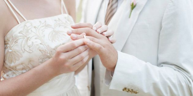 Bride putting ring on grooms