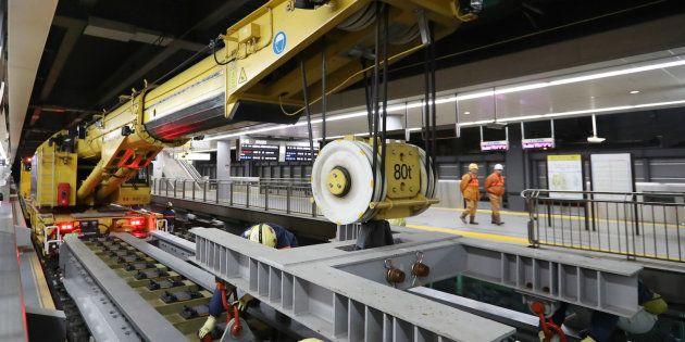 リニア中央新幹線品川駅の新設工事が報道陣に公開され、作業を進めるクレーン車。重さ約130トンのドイツ・キロフ社製の鉄道クレーンで、最大80トンの物体をつり上げることができる=25日未明、東京都港区のJR品川駅