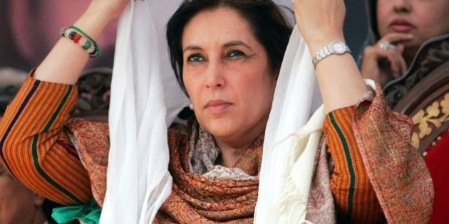 Former Pakistani Prime Minister Benazir Bhutto adjusts her scarf at a campaign rally in Pabbi, 120 kilometers...