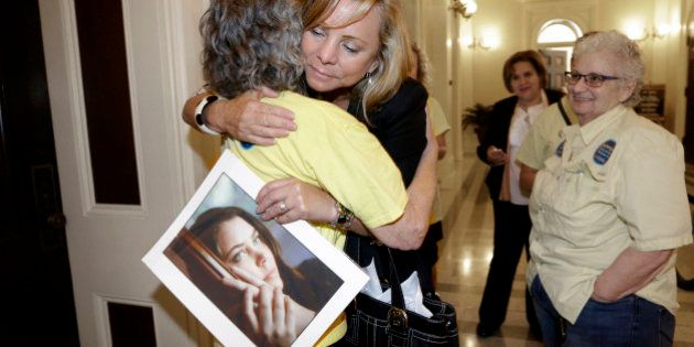 FILE - In this Sept. 9, 2015, file photo, Debbie Ziegler holds a photo of her daughter, Brittany Maynard,...