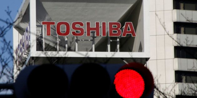The logo of Toshiba Corp is seen behind a traffic signal at its headquarters in Tokyo, Japan January...