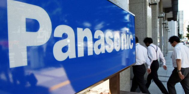 Pedestrians walk past the Panasonic Corp. logo outside the company's office in Tokyo, Japan, on Tuesday,...