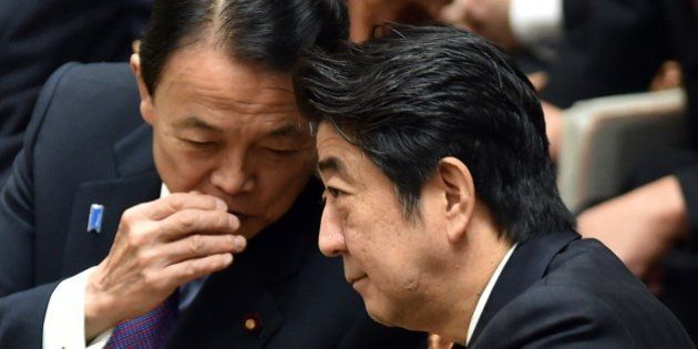 Japanese Minister Shinzo Abe (R) chats with Finance Minister Taro Aso (L) during a budget committee session...