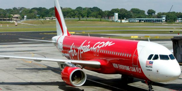 An AirAsia plane taxis on the runway after landing at Singapore's Changi International Airport Friday,...