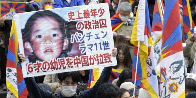 A protester holds a placard with portrait of Dalai Lama's choice for Panchen Lama, Gedhun Choekyi Nyima...