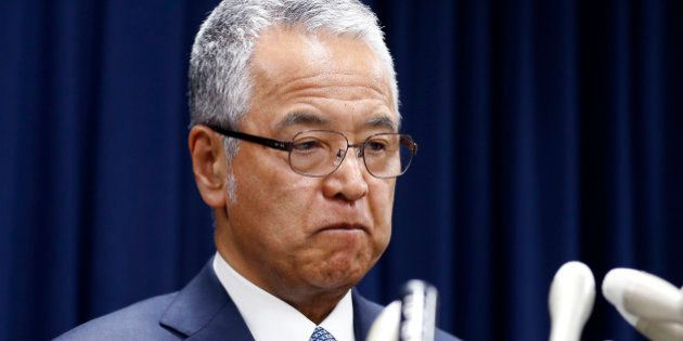 Japanese Economy Minister Akira Amari bites his lips during a nationally televised news conference in...