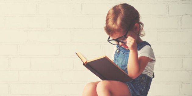 happy child little girl with glasses reading a