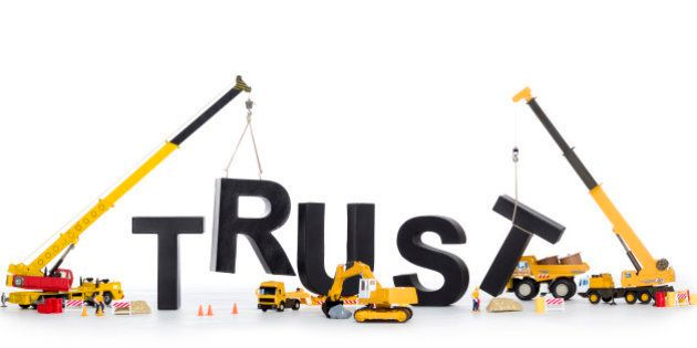 Building up trust concept: Black alphabetic letters forming the word trust being set up by group of construction...