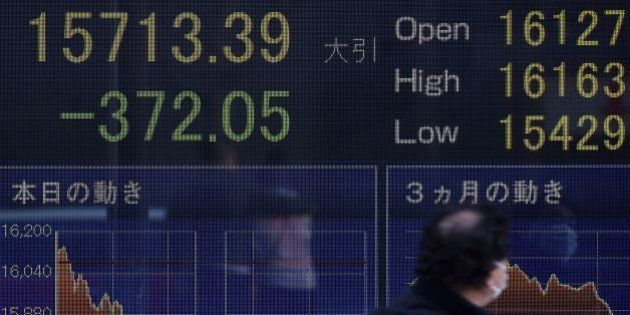 A man walks past an electric quotation board flashing the Nikkei key stock index of the Tokyo Stock Exchange...