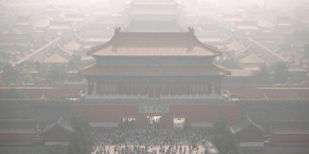 Tourists exit the Forbidden City on a day with high levels of air pollution in Beijing, Monday, Oct....