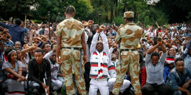 In this photo taken on Sunday, Oct. 2, 2016, Ethiopian soldiers try to stop protesters in Bishoftu, Ethiopia....