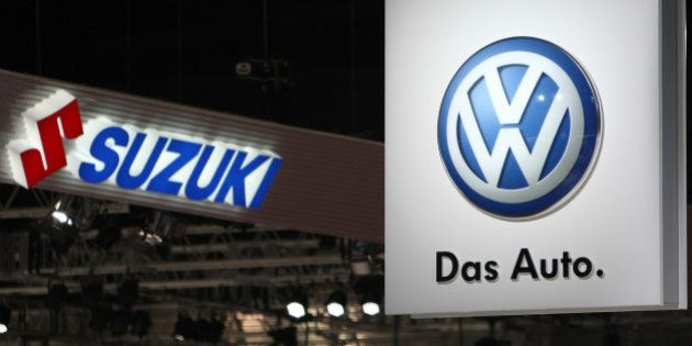 Suzuki Motor Corp., left, and Volkswagen AG (VW) logos are displayed at the Tokyo Motor Show 2011 in...