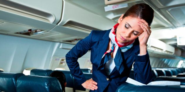 Young air stewardess suffering from headache on an