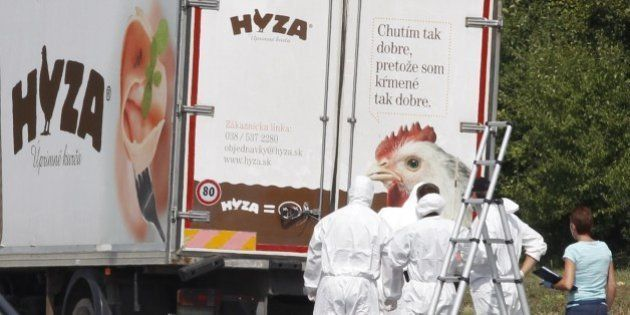 Forensic officers stand in front of a truck inside which were found a large number of dead migrants on...