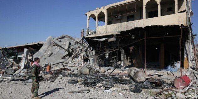 FILE - In this Nov. 13, 2015, file photo, a Kurdish peshmerga fighter stands next to a destroyed building...