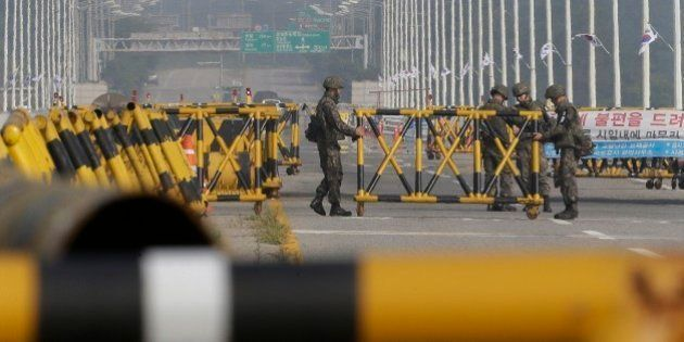 South Korean army soldiers adjust a barricade set up on Unification Bridge, which leads to the demilitarized...