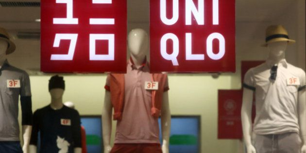 Signage for Uniqlo is displayed in a window of a store, operated by Fast Retailing Co., in Tokyo, Japan,...