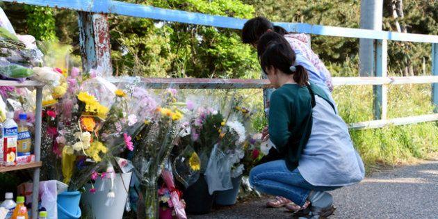 現場付近に置かれた花の前で手を合わせる人たち=2018年5月14日午後4時26分、新潟市西区、田中奏子撮影