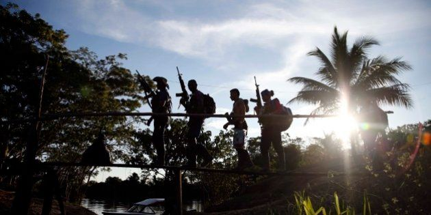 In this Aug. 12, 2016 photo, rebels of the 48th Front of the Revolutionary Armed Forces of Colombia walk...