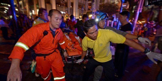 Thai rescue workers carry an injured person after a bomb exploded outside a religious shrine in central...
