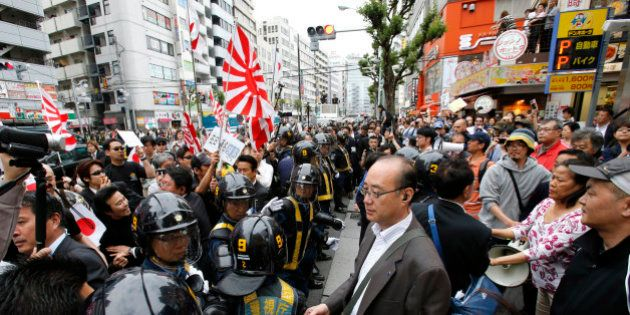 In this photo taken Sunday, May 19, 2013, nationalist protesters with Japanese flags and Japan's naval...