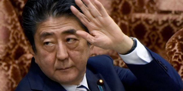 Japanese Prime Minister Shinzo Abe raises his hand before answering questions during the budget committee...