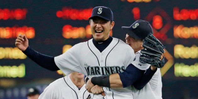 Seattle Mariners starting pitcher Hisashi Iwakuma is hugged by first baseman Logan Morrison, right, after...