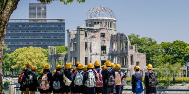 Children standing near Atomic Bomb memorial in Hiroshima, Japan. A-Bomb (Genbaku) Dome, Hiroshima, Japan....